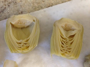 The artichoke heart on the left has had the inner leaves removed - the one on the right has not.